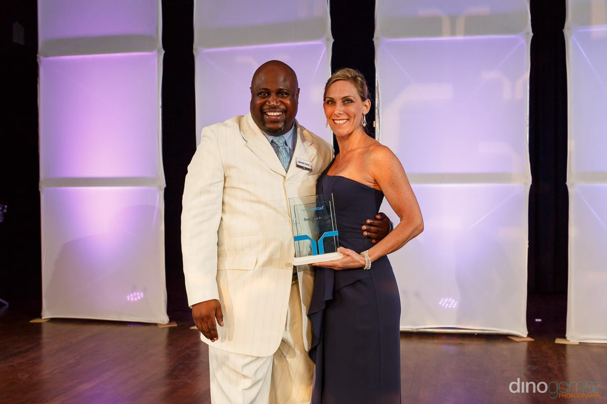 A smiling woman and man with an award at Randstad Cabo 2014 - Secrets Pue, taken by Dino Gomez