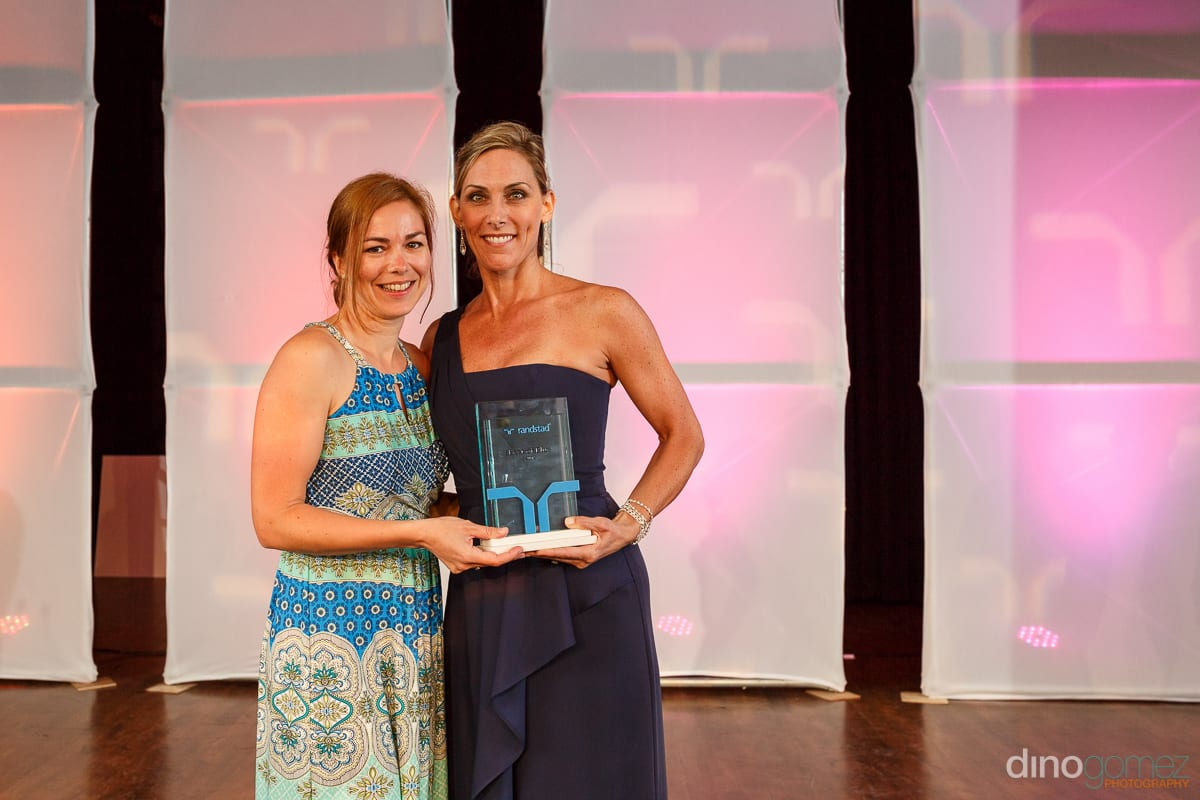 Two women in beautiful gowns holding an award at Randstad Cabo 2014 - Secrets Pue taken by Dino Gomez