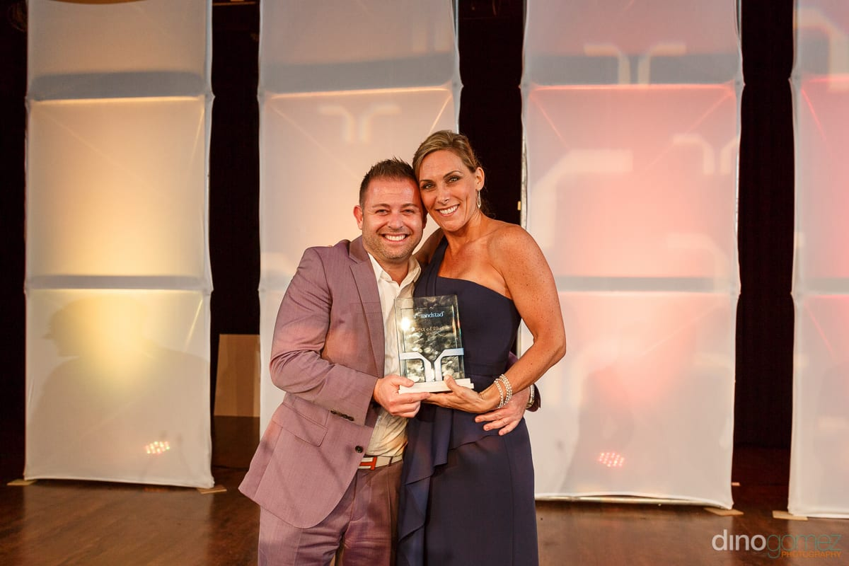 A man in a lilac suited and a woman in a blue gown bith smiling and holding an award at Randstad Cabo 2014 - Secrets Pue