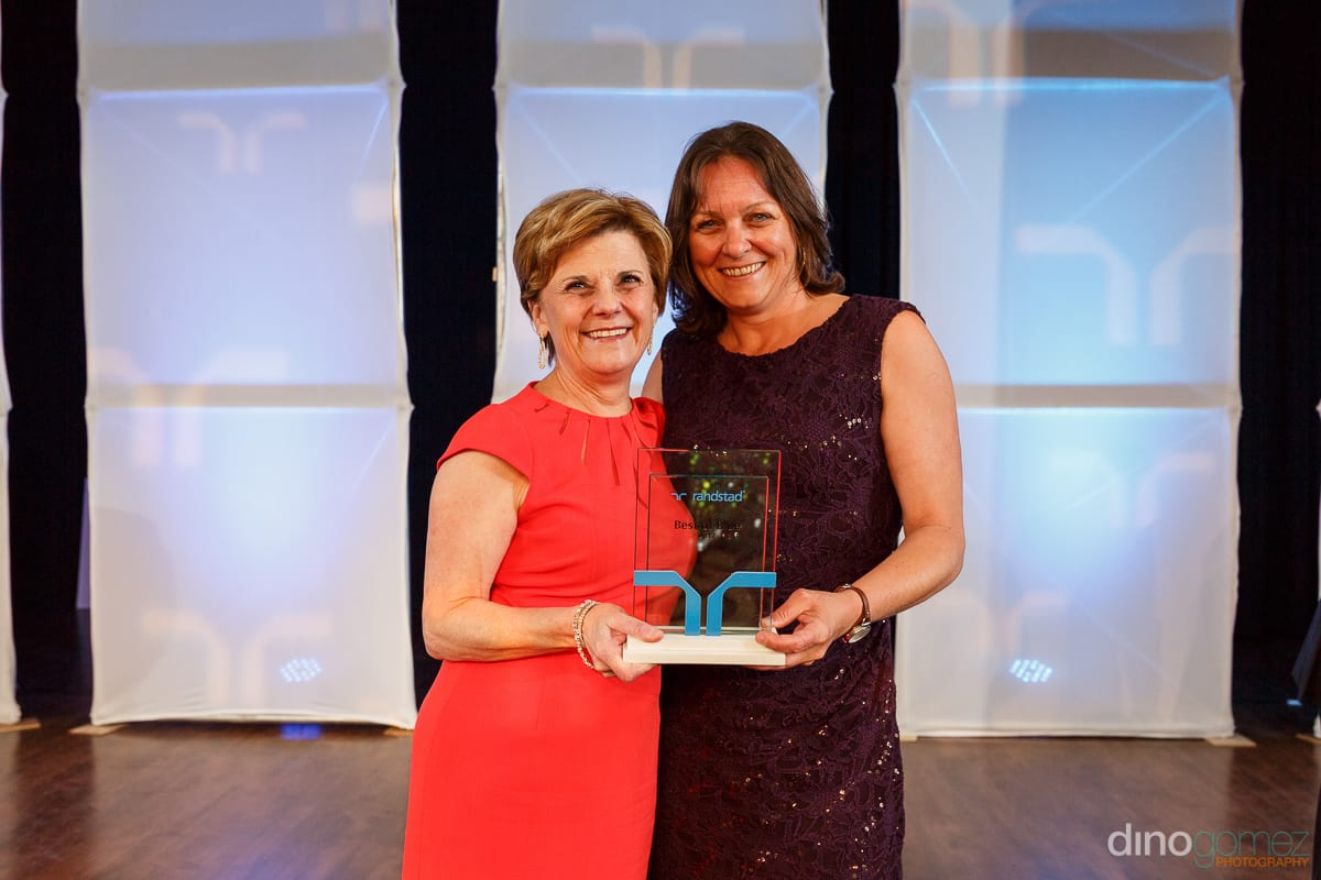 One woman in a red dress and another in a black dress holding an award at Randstad Cabo 2014 - Secrets Pue