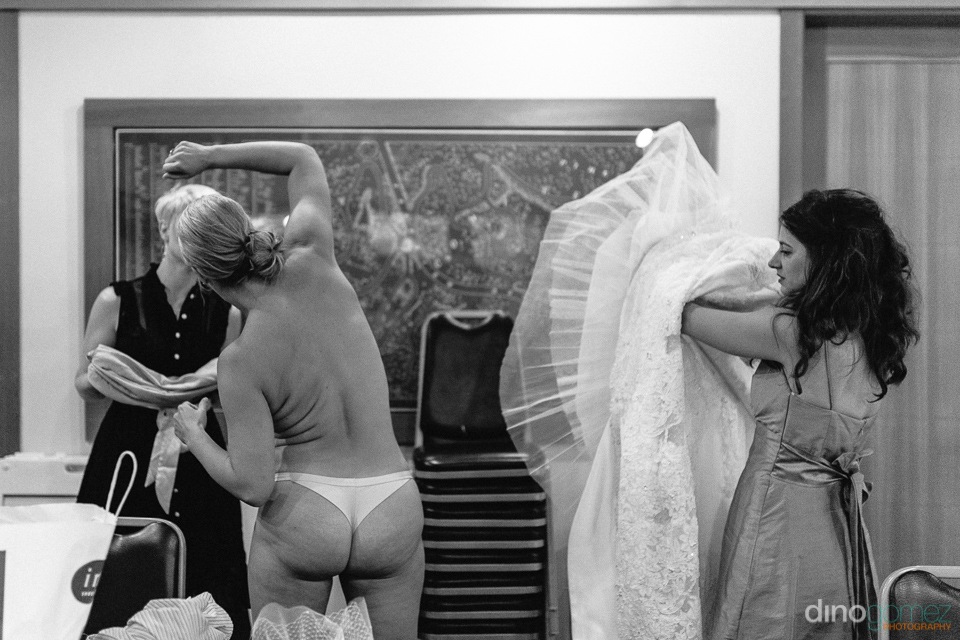 Fun photo of bride stretching to put her dress on