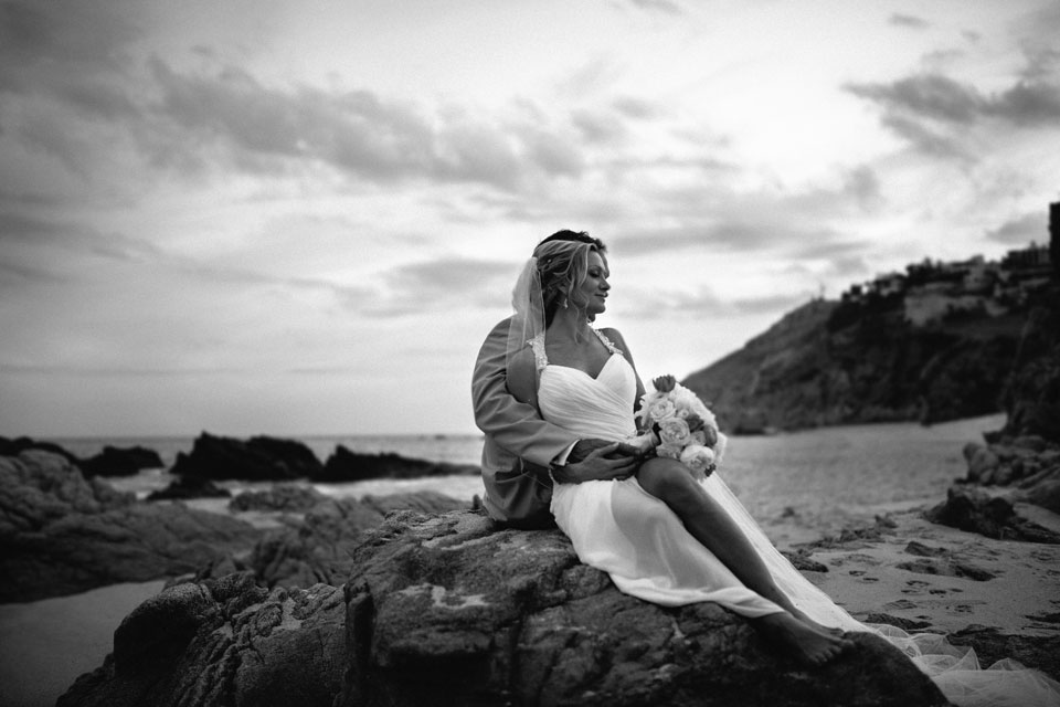 Beautiful black and white shot of a bride and groom sitting on a beach rock by high end destination wedding photographer in Mexico Dino Gomez