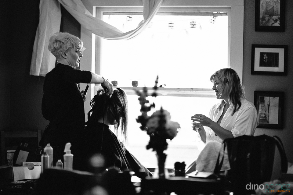 Maid of honour getting her hair done with bride