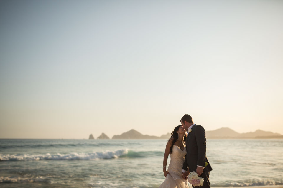 The newlyweds leaning in before the kiss on the beach in Mexico