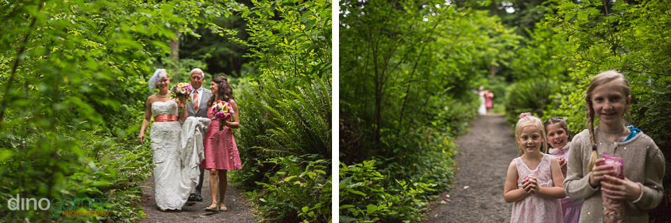 Bride walking with dad and the maid of honour in the woods and three little girls standing in a pathway