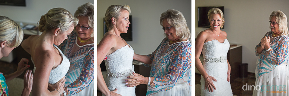 The bride getting dressed on her wedding day with mom