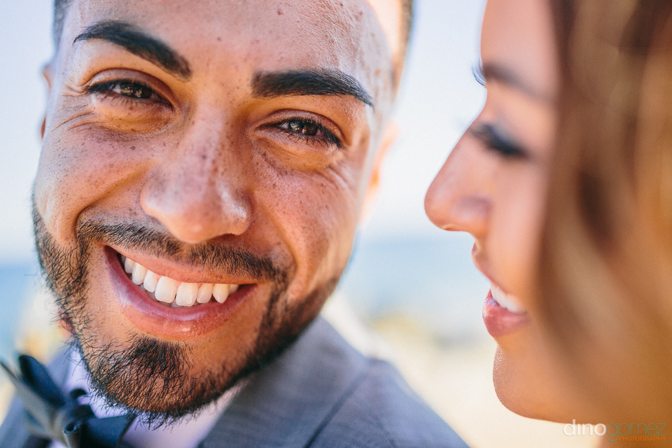 groom looking into camera with bride