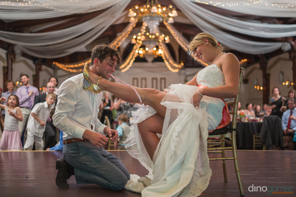 groom removing the garter from the bride at the Elysian ballroom