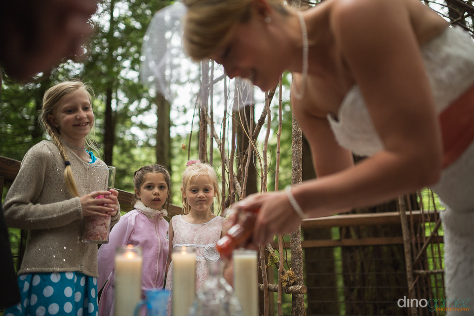 kids looking at bride lighting a candle