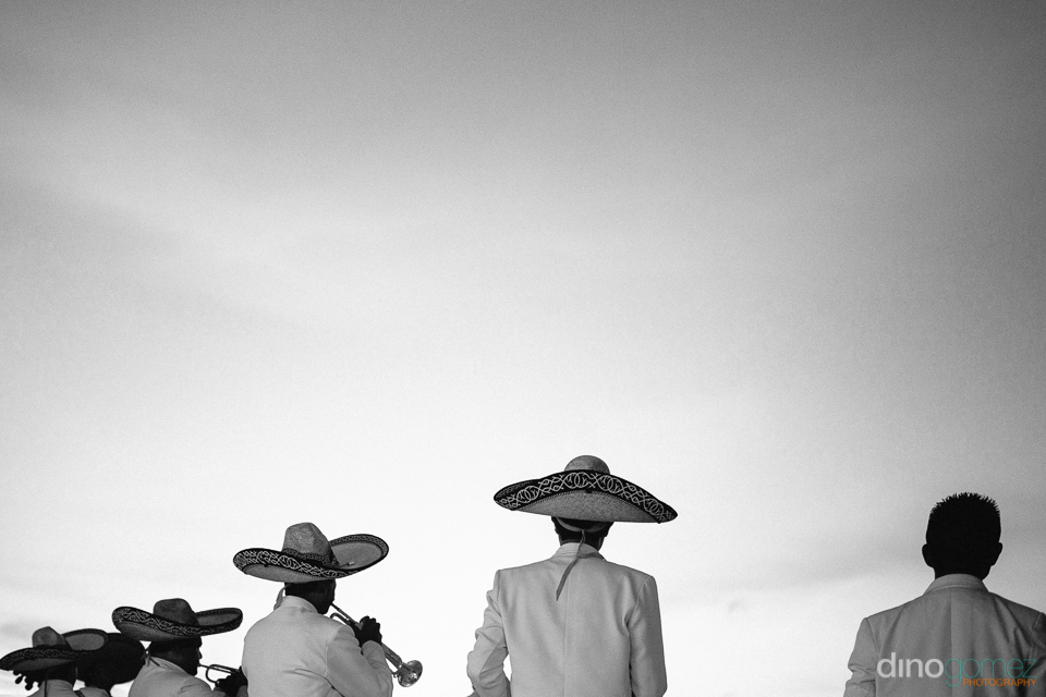 black and white photo of a mariachi band from behind