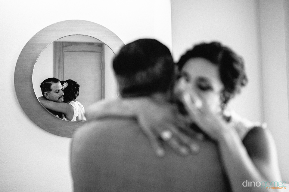 bride hugging her dad and crying father reflection on a mirror