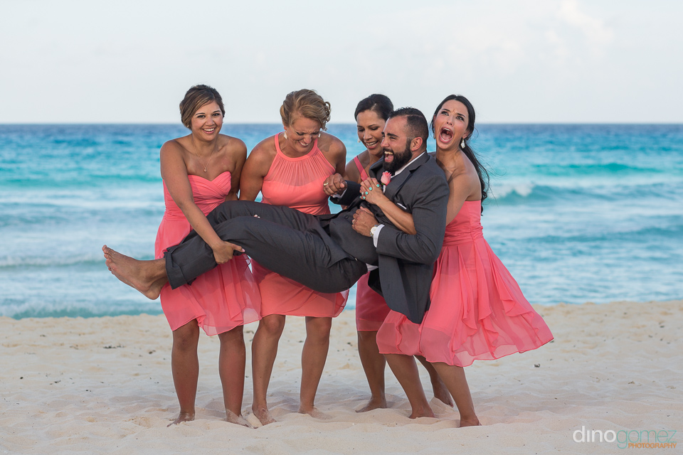bridesmaids lifting the groom on the beach with fun facial expre