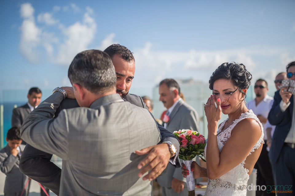 father of the bride hugs groom after delivering her and she is c