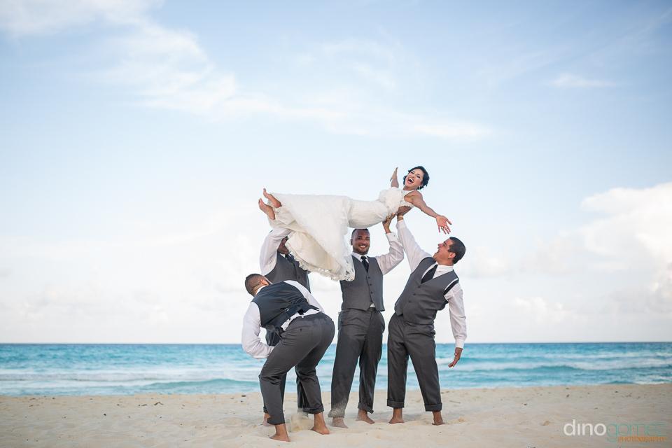 groomsmen lifting the bride on the beach and the groom peeking u