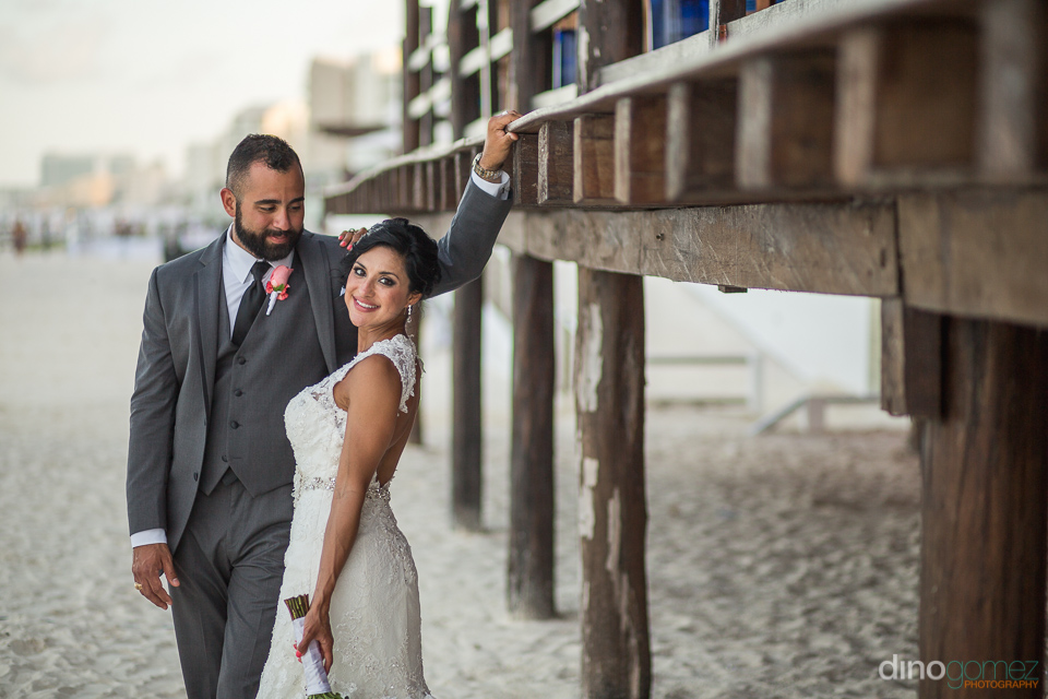 photo of bride and groom next to a deck on the beach