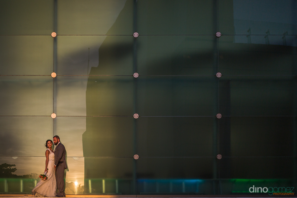 photo of the bride and groom lit by the sunset against a glass w