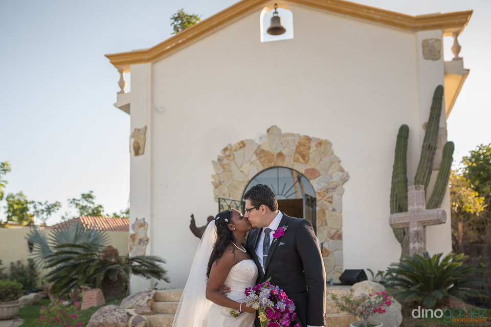 bride and groom kissing in front of a church - Wedding Photograp