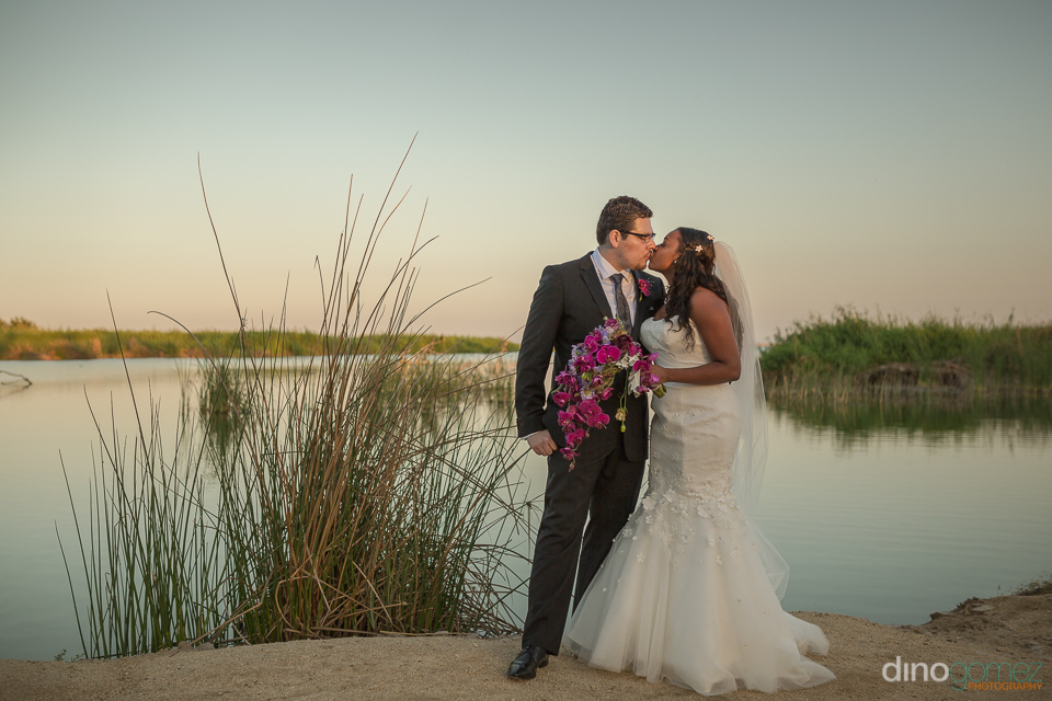 bride and groom kissing next to a pond - Wedding Photographer in
