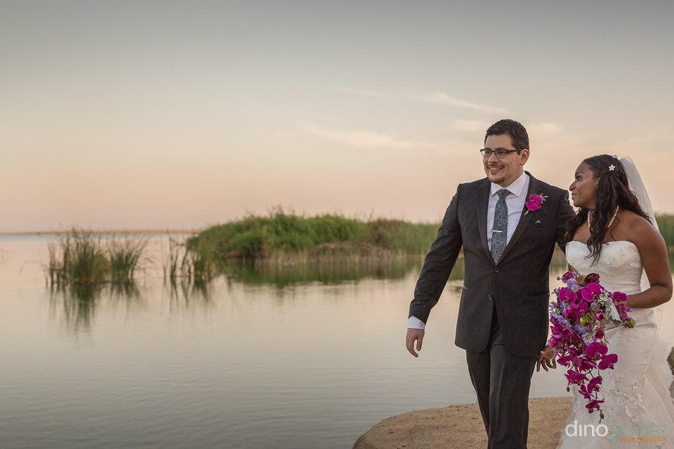 bride and groom walking next to a pond - Wedding Photographer in