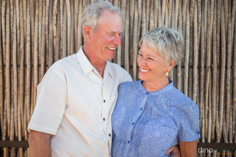 couple laughing against a wooden wall