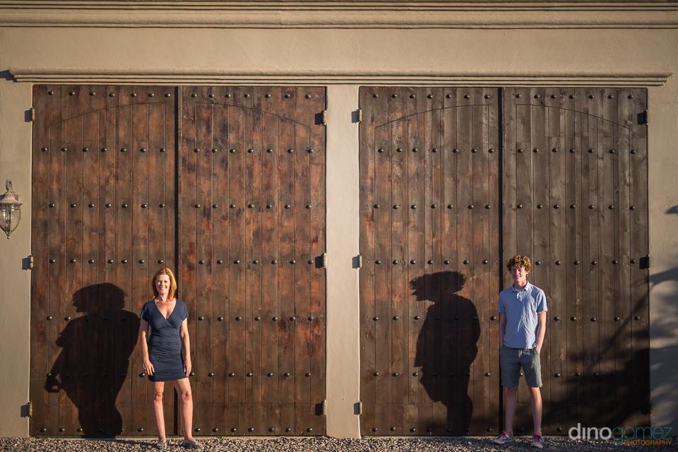 couple standing in from of two bid wooden doors