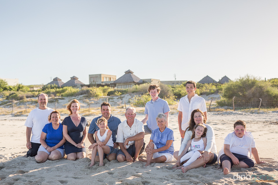 family sittion on the sand during a family photo session