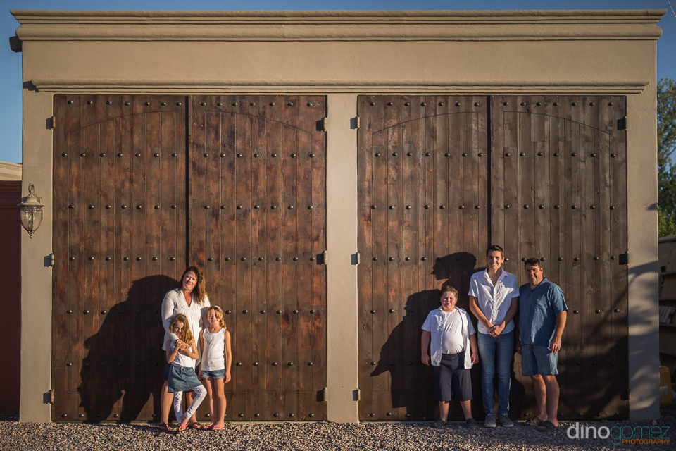 family standing in front of two big wooden doors