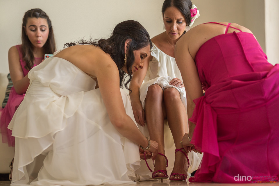 Photograph of the bride putting her shoes on by Dino Gomez