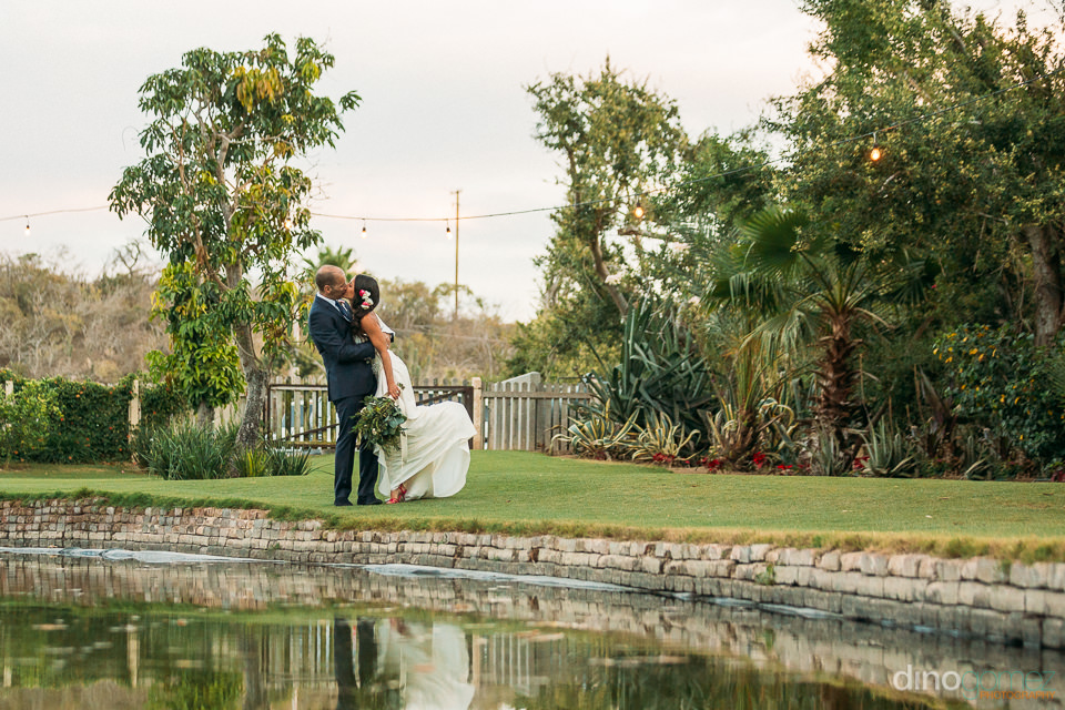 Euphoric kiss of bride and groom next to a lake at flora farm