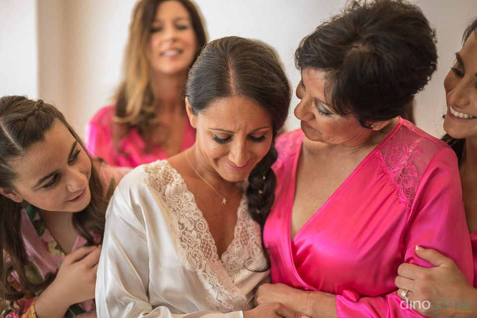 Mom hugging crying bride while getting ready