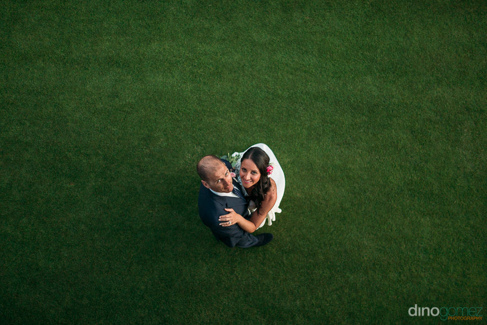 aerial photo of the bride and groom on the grass