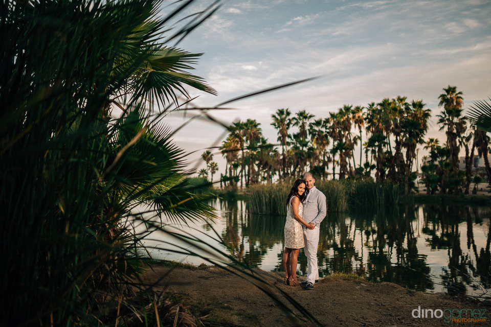 couple hugging by the side of a pond at the Estero San Jose in L