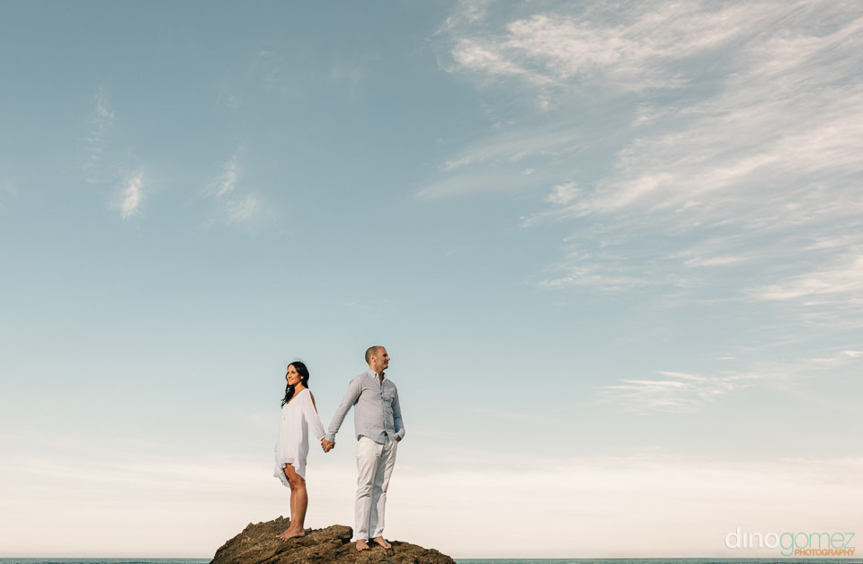couple on top of a mountain overlooking the sea in Los Cabos Mex