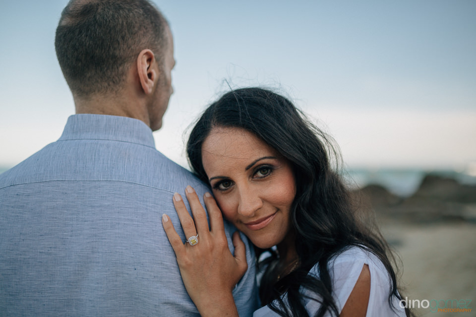 woman leaning on fiances shoulder during their engagement sessio