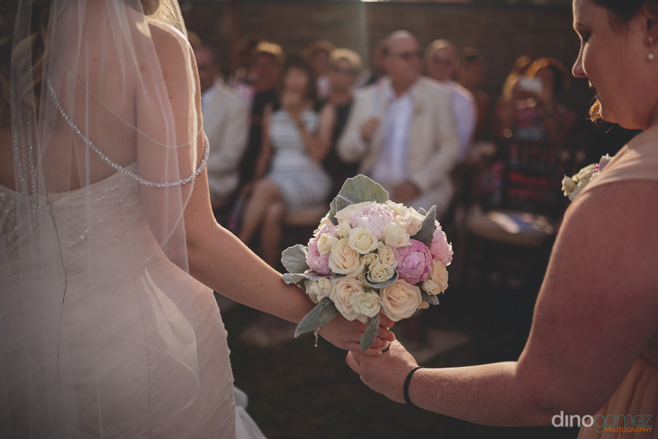 bride passes bridal bouquet to bridesmaid