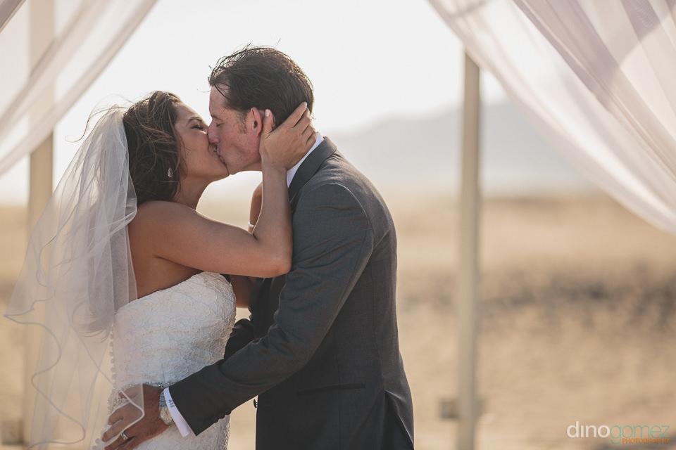 The Bride and Groom kiss on the Cabo San Lucas beach