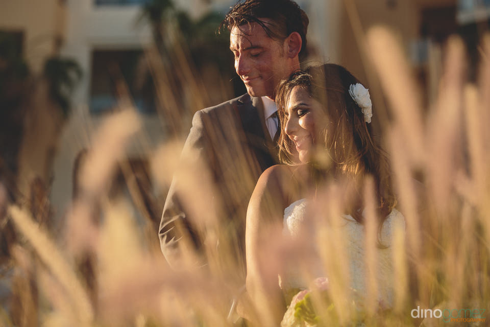 Wedding couple hug in tall Cabo beach grass