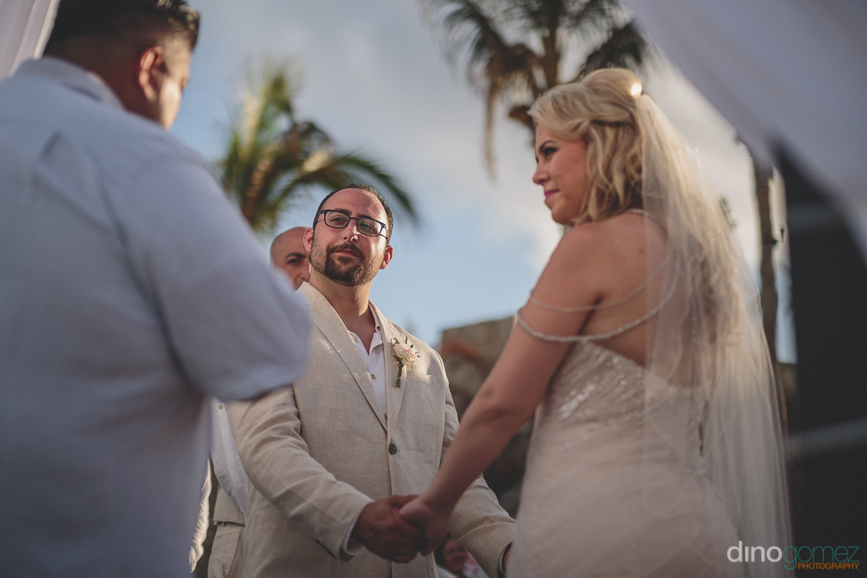bride and groom holding hands cabo beach wedding