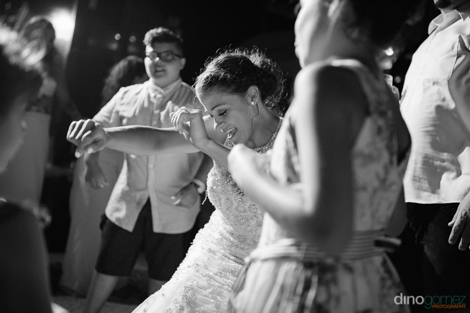 Black and white wedding photo of bride dancing