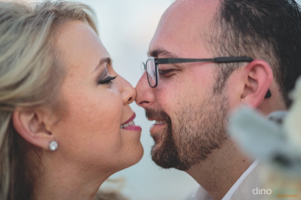 newlyweds touch noses cabo wedding photo