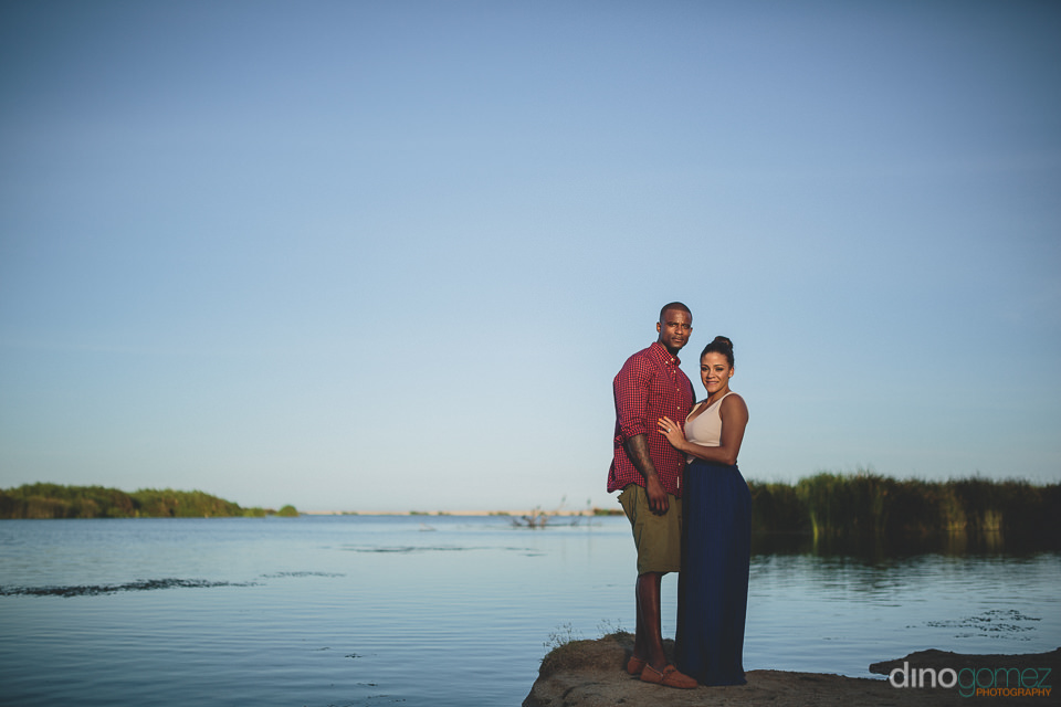 Bride and groom pose in front of tranquil Cabo water