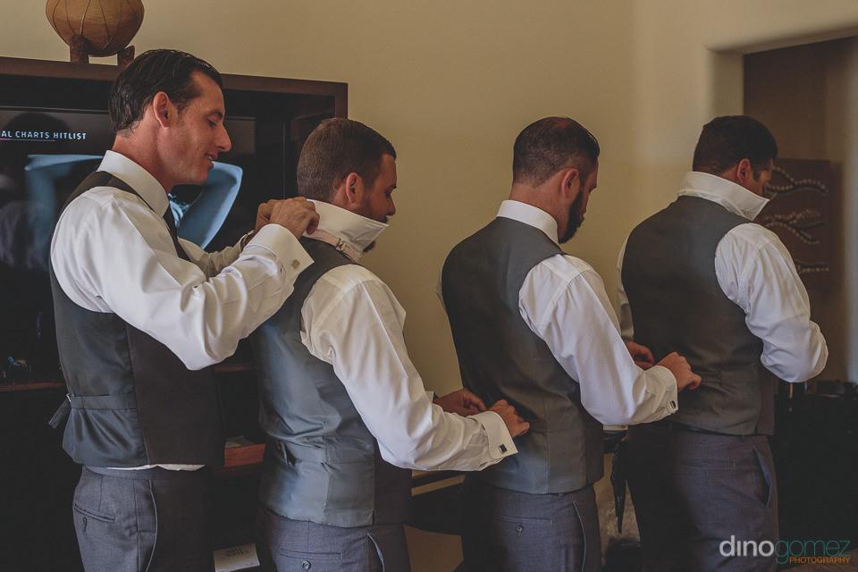 Groomsmen tying their vests