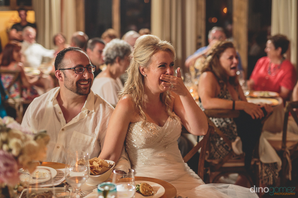cabo bride laughs during wedding dinner