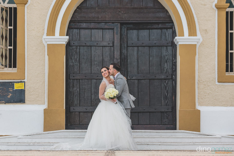 newlyweds pose in front of mision san jose del cabo church