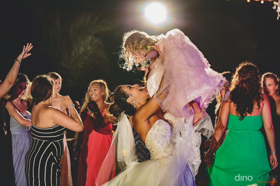 flower girl lifted by bride during cabo wedding