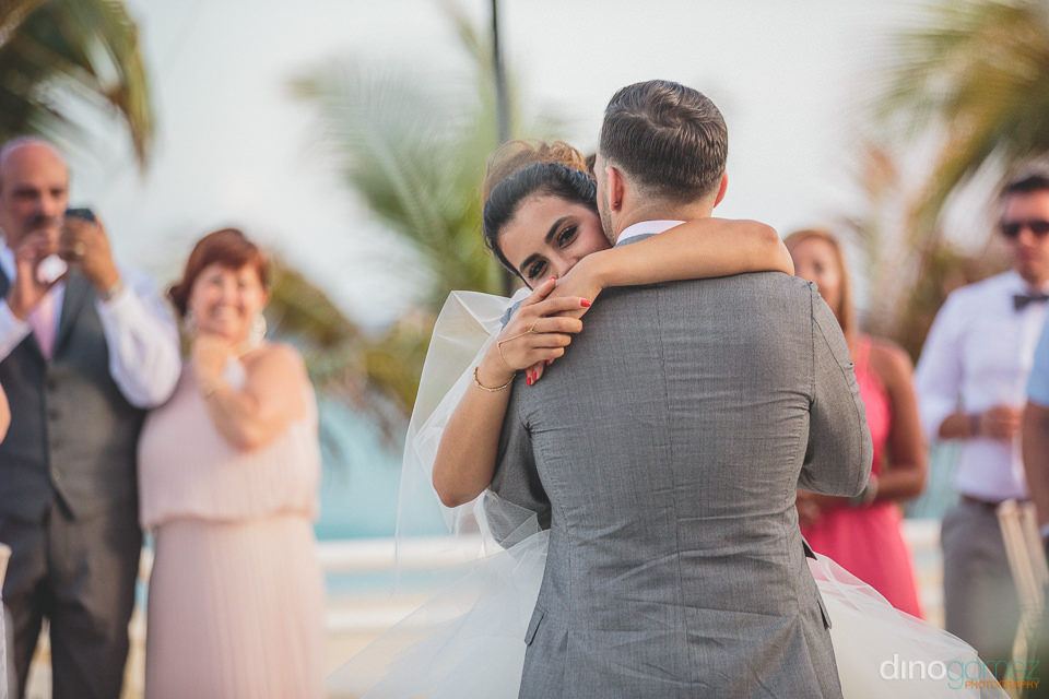 husband and wife hug while wedding guests take their photo