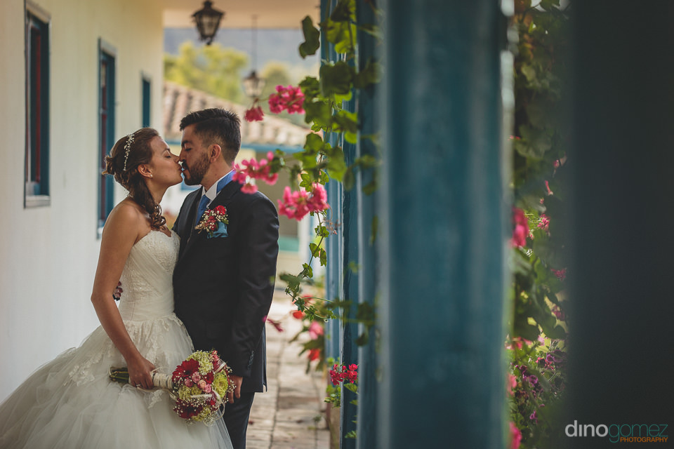 newlyweds kiss outside of their colombian hacienda