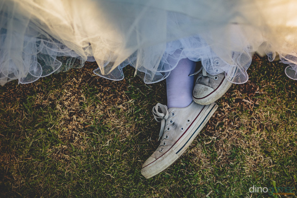 bride wearing fun casual shoes at her outdoor wedding