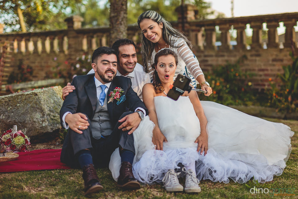newlyweds and guests take selfie photo at wedding