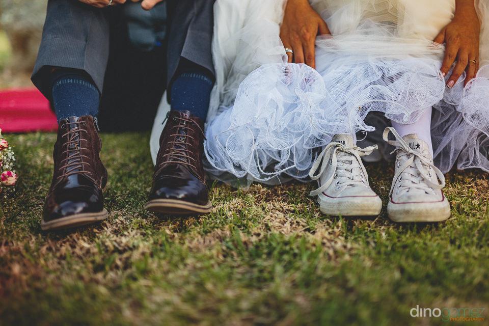 groom wears dress shoes while bride wears sneakers at wedding